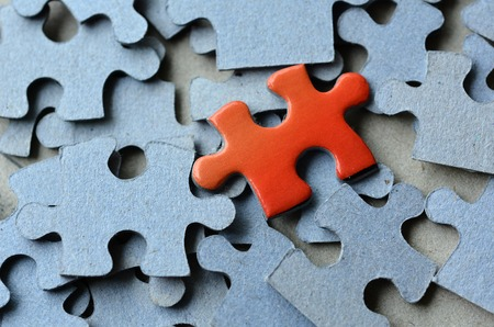 leadership qualities: Orange puzzle pice standing above the rest of puzzle pieces.