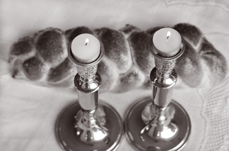 challah: Lit Shabbath candles with uncovered challah bread and kippah. (BW) Stock Photo