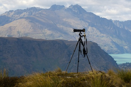 telephoto: Professional camera with telephoto lens on a tripod during landscape photography outdoor. Stock Photo