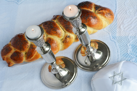 challah: Shabbat eve table with uncovered challah bread, lit Sabbath candles and kippah.