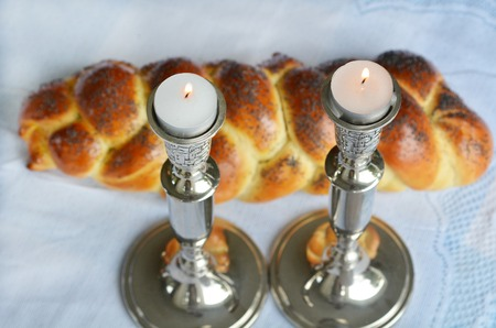jewish home: Lit Shabbath candles with uncovered challah bread and kippah.