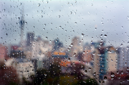 Urban view of rain drops falls on a window during a stormy day overlooking Auckland CBD New Zealand skyline in the background. Stock Photo