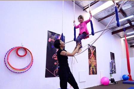 Little child (girl age 05)   learn circus skills on static trapeze from circus instructor.