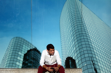 financial district: One young Indian business man talks on a smartphone outdoors  alone in city financial district street. Mobile communication concept Stock Photo