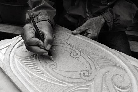 maories: AUCKLAND - 21 de agosto 2015: maor�es manos del hombre de dibujo patrones de los maor�es de madera carving.Maori son el pueblo ind�gena de Nueva Zelanda, pa�s de origen Polinesia, emigr� a Nueva Zelanda hace m�s de 1000 a�os.