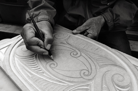 maori: AUCKLAND - AUG 21 2015:Maori man hands drawing patterns of Maori Wood carving.Maori are the indigenous people of New Zealand Originally from Polynesia, migrated to New Zealand over 1000 years ago.