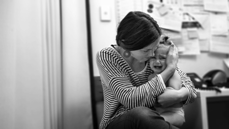 Young mother hugs a crying toddler in hospital. Child healthcare concept