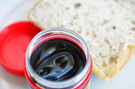 distinctive flavor: Marmite food spread close up against slices of sandwich bread for breakfast.