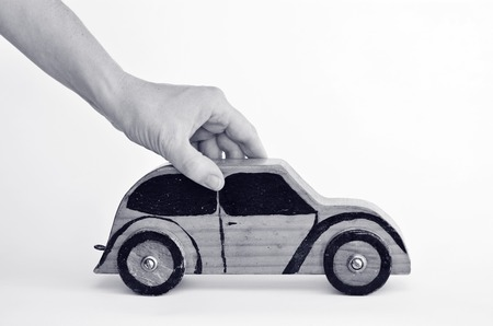 safe driving: Woman hands holds toy car on white background-copy space.Concept photo of car business,car Insurance, auto dealership,car rental ,safe driving ,buying, renting, fuel, service and repair costs (BW)