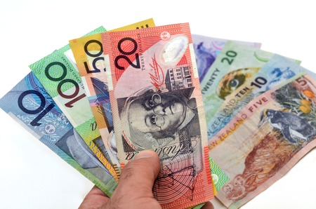australian dollar notes: Mans hand holds Australian Dollar banknotes against New Zealand Dollar bank notes. Concept photo of money, banking ,currency and foreign exchange rates.  (Isolated on white background) Stock Photo