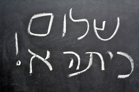 Hello First Grade greetings in Hebrew Shalom Kita Alef on a chalkboard in Israeli primary school at the beginning of the school year.Concept photo of early age education,learning ,studying, teaching