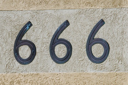 antichrist: Display number 666 sign and symbol on a wall background. Concept photo of religion, hell, satan, superstition, belief.