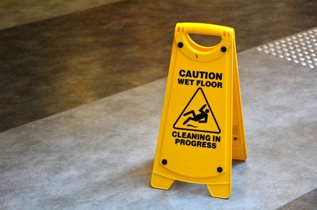 building maintenance: Slippery floor surface warning sign  and symbol in building, hall, office, hotel , restaurant, restroom. Concept photo danger.