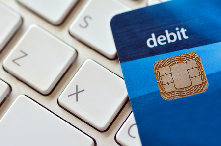 debit card: Close up of debit card on a computer keyboard. Concept of Internet purchase  and online shopping. Stock Photo