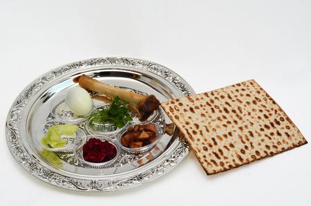 유월절 유대인 휴일에 seder 식사 도중 사용 된 일곱 번째 상징적 인 품목을 가진 Passover Seder 격판 덮개의 옆에 Matzo 빵. 흰색 배경 복사 공간