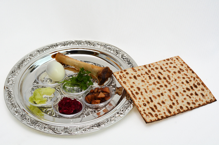 Matzo bread next to Passover Seder Plate with The seventh symbolic item used during the seder meal on passover Jewish holiday. White background with copy space Archivio Fotografico