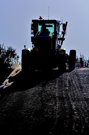 grader: Silhouette of a Grader working at road construction site.