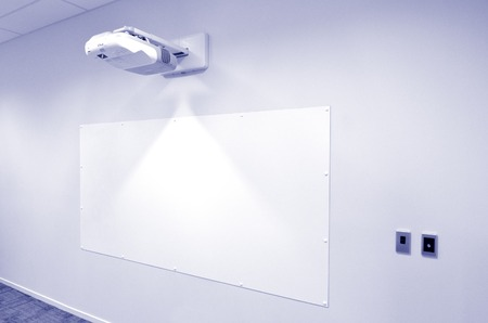 Projection screen with video image projector hung on a wall of meeting room.  Concept photo of business workplace. copy space Stockfoto