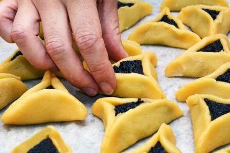 haman: Woman hands cooking Hamentashen, Ozen Haman, cookies for Purim Jewish holiday.