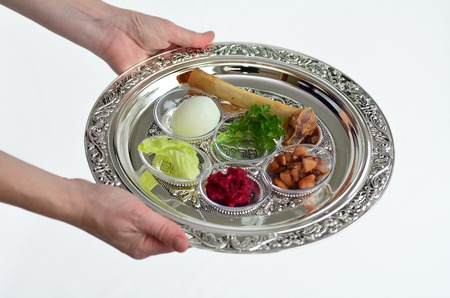 seder: Jewish woman hands carry Passover Seder Plate with The seventh symbolic item used during the seder meal on passover Jewish holiday.White background with copy