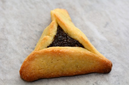 hamantash: One backed Hamentashen, Ozen Haman, Purim cookie for the Jewish holiday Purim. Isolated on baking paper. (Copy space) Stock Photo