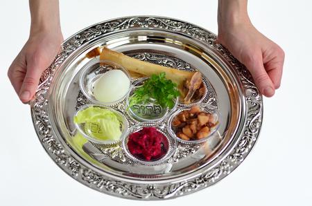 ユダヤ人の女性の手は、ユダヤ人の休日の過越でセダー食事中に使用される第 7 の象徴的な項目と過ぎ越しの祝いの祭文プレートを運ぶ。白の背景