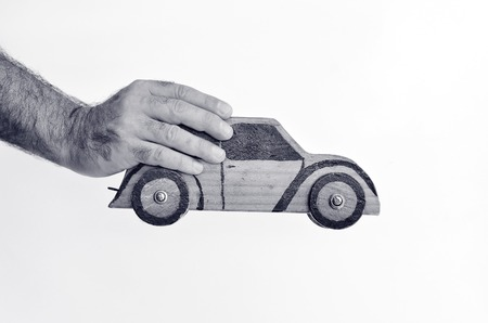 safe driving: Hand holds toy car isolated on white background - copy space.Concept photo of car business,car Insurance, auto dealership,car rental ,safe driving ,buying, renting, fuel, service and repair costs (BW)