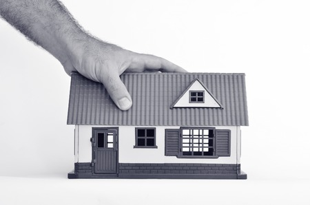 homeownership: Man hand holds toy house isolated on white background - copy space.Concept photo of real estate business, home  Insurance, house rental,buying, renting, mortgage, finance,service and repair costs (BW)