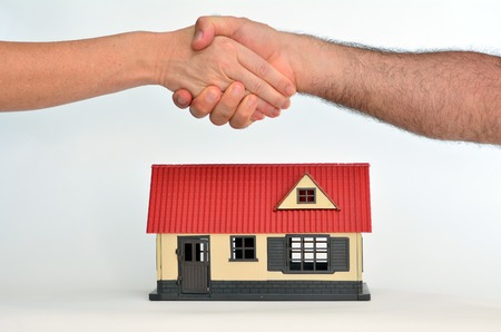 property: Man and a woman shaking hands over a toy house on white background - copy space.Concept photo of real estate business, home  Insurance, house rental, buying, renting, mortgage, selling, finance.