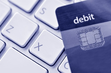 debit card: Close up of debit card on a computer keyboard. Concept of Internet purchase  and online shopping. (BW) Stock Photo
