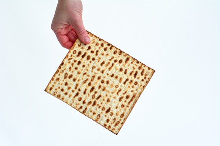 matzes: Jewish woman hand holds leavened bread, matza on white background with copy space