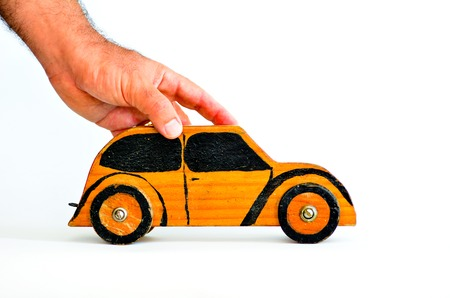 Renting: Man hands holds toy car on white background-copy space.Concept photo of car business,car Insurance, auto dealership,car rental ,safe driving ,buying, renting, fuel, service and repair costs. Stock Photo