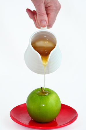 honey pot: Jewish woman hand holds honey pot and pour fresh honey with on green apple during Rosh Hashanah Jewish holiday, on white background with copy space