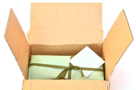 life events: Olive green gift box with dark green ribbon and bow with gift card inside a cardboard delivery box.Concept photo of birthday, holidays, life events, wedding and special occasion