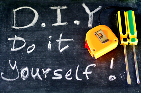 modifying: Do It yourself ( D.I.Y ) Handwritten with white chalk on a blackboard with working tools.concept photo of home repairing and maintenance Stock Photo
