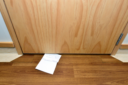 slipped: Message slipped under wooden door. Concept photo Stock Photo