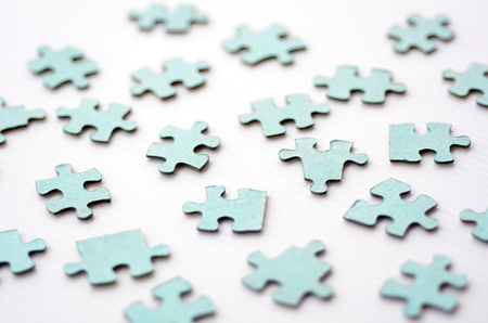 randomness: Scattered puzzle pieces toy isolated on white background. Concept photo of disharmony, change, no-order and chaos. Stock Photo