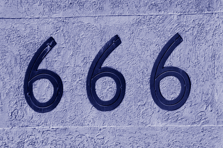 superstition: Display number 666 sign and symbol on a wall background. Concept photo of religion, hell, satan, superstition, belief.