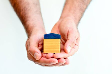 Renting: Man hands holds toy house isolated on white background with copy space.Concept photo of real estate business, home Insurance, house rental,buying, renting, mortgage, finance,service and repair costs Stock Photo