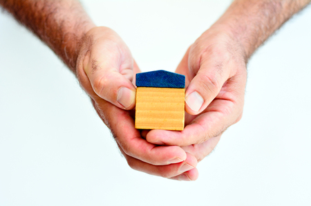 homeownership: Man hands holds toy house isolated on white background with copy space.Concept photo of real estate business, home Insurance, house rental,buying, renting, mortgage, finance,service and repair costs Stock Photo