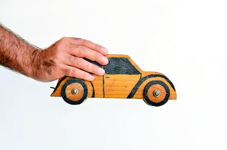 safe driving: Hand holds toy car isolated on white background with copy space.Concept photo of car business, car Insurance, auto dealership,car rental ,safe driving ,buying, renting, fuel, service and repair costs Stock Photo