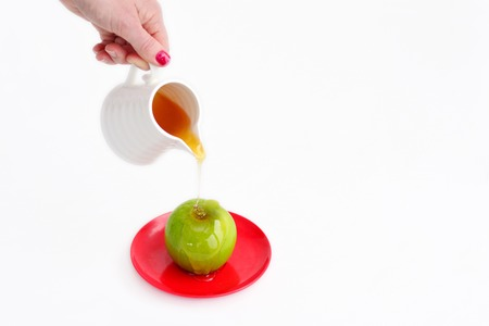 jewish holiday: Jewish woman hand holds honey pot and pour fresh honey with on green apple during Rosh Hashanah Jewish holiday, on white background with copy space