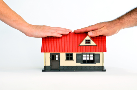 homeownership: Couple touch a toy house isolated on white background - copy space.Concept photo of real estate business, home  Insurance, house rental,buying, renting, mortgage, finance,service and repair costs