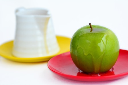 honey pot: Green apple coverd in honey next to honey pot on Rosh Hashanah Jewish holiday.White background with copy space