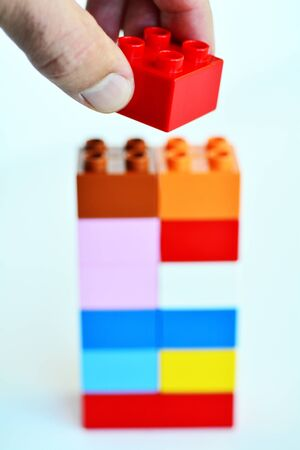 red building blocks: Mans hand puts a red toy block on top of a building blocks tower in the background. concept photo of imagination, creativity, planning and ideas