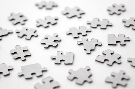piezas de rompecabezas: Dispersos juguete piezas del rompecabezas aislados sobre fondo blanco. Foto del concepto de la falta de armonía, el cambio, sin orden y el caos. (BW)