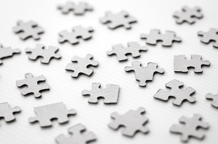 chaos: Scattered puzzle pieces toy isolated on white background. Concept photo of disharmony, change, no-order and chaos. (BW) Stock Photo