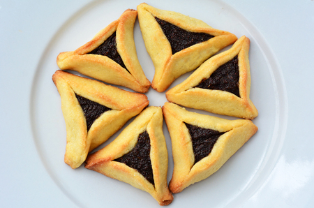 haman: Six Backed Hamentashen, Ozen Haman, Purim cookies designed in Hexagon shape on a white plate for the Jewish holiday Purim.(Copy space)