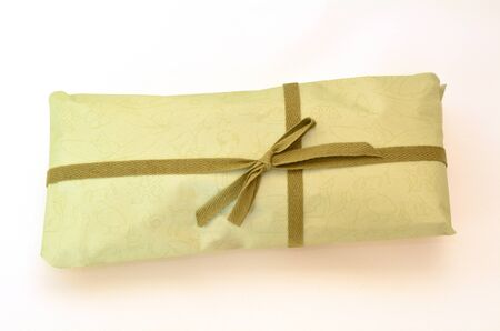 life events: Olive green gift box with dark green ribbon and bow on white background with copyspace.Concept photo of birthday, holidays, life events, wedding and special occasion