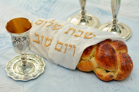 Shabbat eve table with covered challah bread, Sabbath candles and Kiddush wine cup. Stockfoto